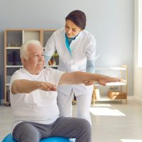 Attentive experienced physiotherapist woman trains a senior man sitting on fitness ball in a room, supporting his outstretched arms. Senior retirement home service, care taker concept.
